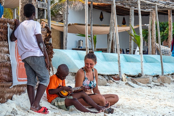White woman with two black kids on the beach in Africa