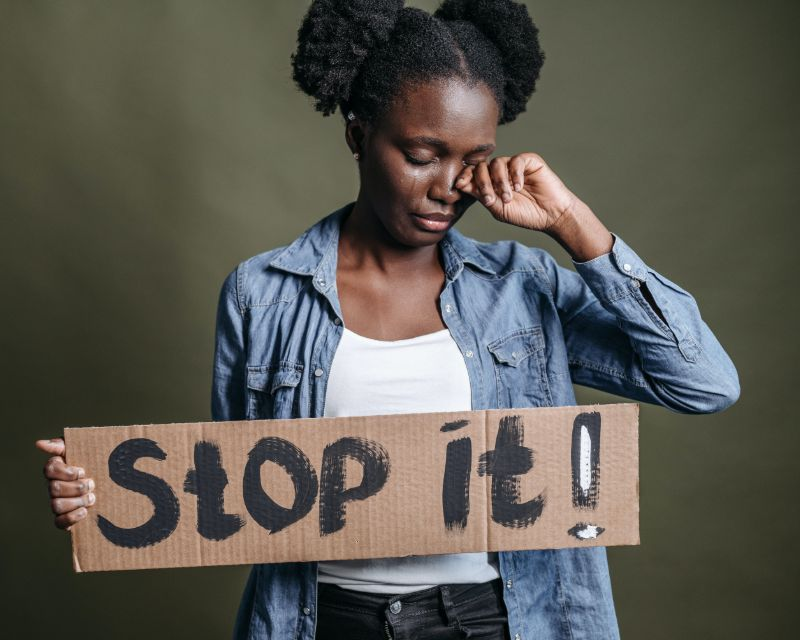 Ethiopian girl crying while holding a stop-it placard